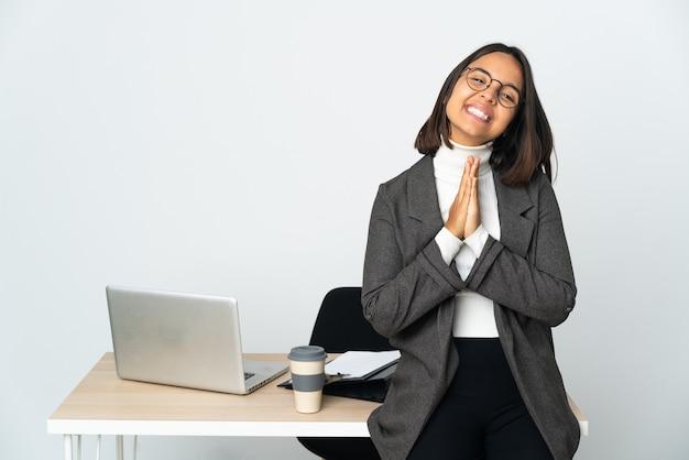 La giovane donna di affari latina che lavora in un ufficio isolato su fondo bianco tiene insieme il palmo. la persona chiede qualcosa