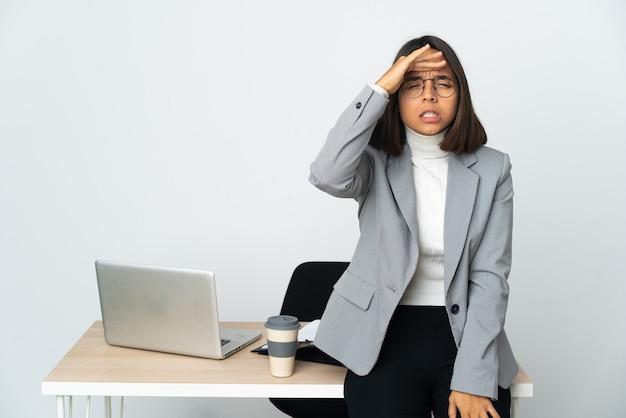 Giovane donna d'affari latina che lavora in un ufficio isolato su sfondo bianco guardando lontano con la mano per guardare qualcosa