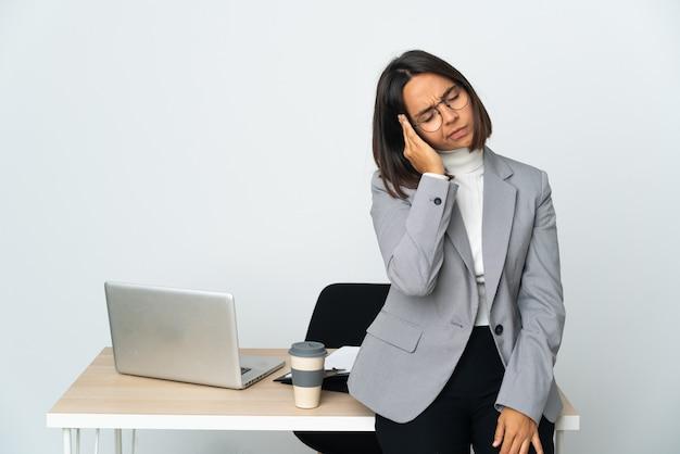 Giovane donna d'affari latina che lavora in un ufficio isolato su sfondo bianco con mal di testa