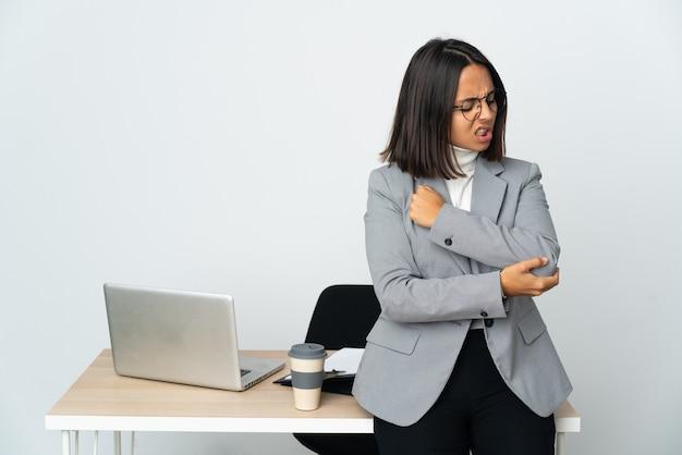 Giovane donna d'affari latina che lavora in un ufficio isolato su sfondo bianco con dolore al gomito