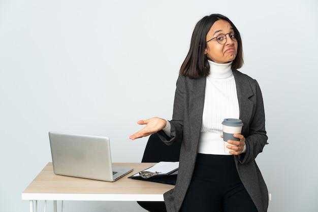 Giovane donna latina di affari che lavora in un ufficio isolato sul muro bianco felice e sorridente