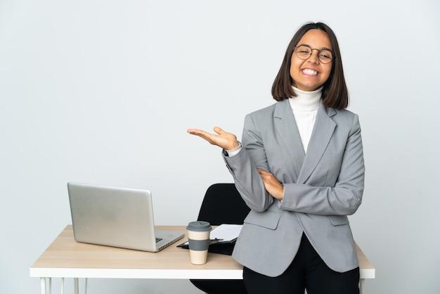Giovane donna latina di affari che lavora in un ufficio isolato sul muro bianco che tiene il copyspace immaginario sul palmo per inserire un annuncio