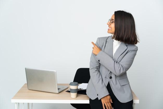 Giovane donna latina di affari che lavora in un ufficio isolato sulla parete bianca che indica indietro