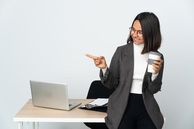 Giovane donna latina di affari che lavora in un ufficio isolato sulla parete bianca che indica il dito a lato e che presenta un prodotto