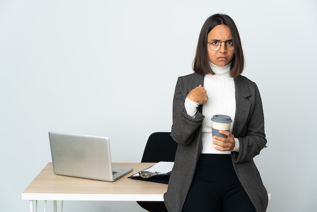 Giovane donna latina di affari che lavora in un ufficio isolato sul muro bianco che punta a se stessi