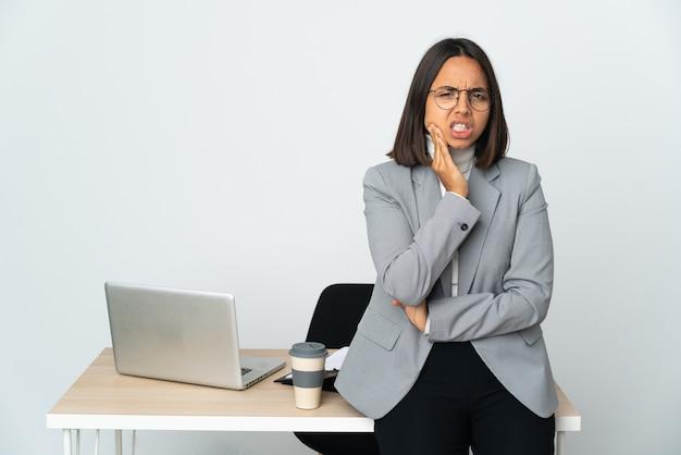 Giovane donna latina di affari che lavora in un ufficio isolato sul muro bianco con mal di denti