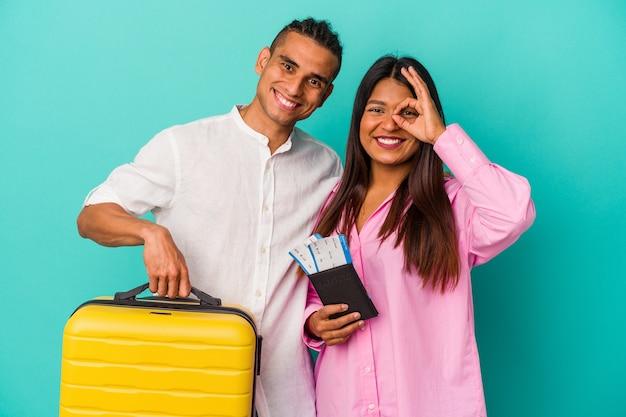 Giovane coppia latina che va a viaggiare isolata su sfondo blu eccitata mantenendo il gesto ok sull'occhio.