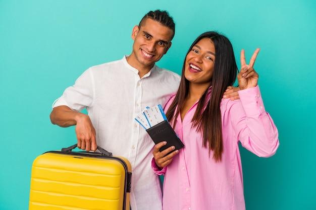 Giovane coppia latina che va a viaggiare isolata su sfondo blu gioiosa e spensierata che mostra un simbolo di pace con le dita.
