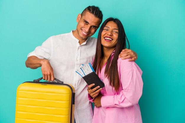 Giovane coppia latina che va a viaggiare isolata su sfondo blu ridendo e divertendosi.