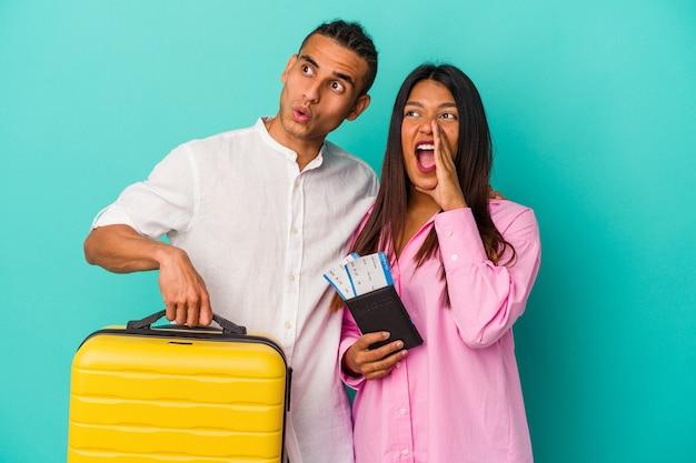 Giovane coppia latina che va a viaggiare isolata su sfondo blu gridando e tenendo il palmo vicino alla bocca aperta.