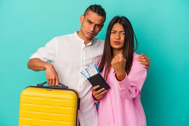 Giovane coppia latina che va a viaggiare isolata sulla parete blu che mostra il pugno alla telecamera, espressione facciale aggressiva.