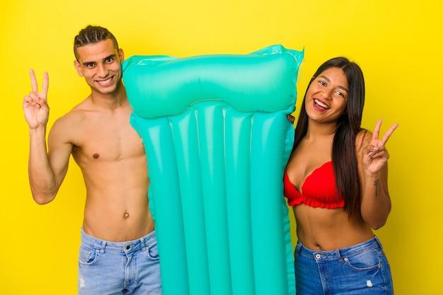 Giovane coppia latina che tiene materasso ad aria isolato su sfondo giallo gioioso e spensierato che mostra un simbolo di pace con le dita.