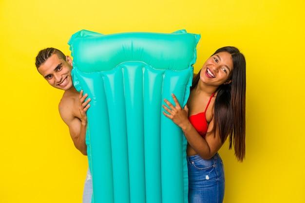 Giovane coppia latina che tiene un materasso ad aria isolato sul muro giallo yellow