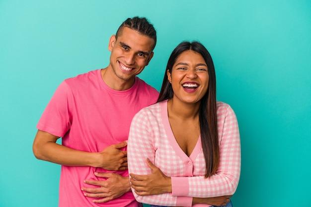 Giovane coppia latina isolata su sfondo blu ridendo e divertendosi.