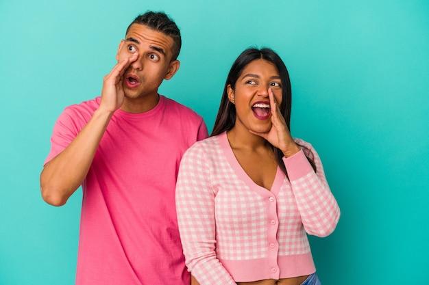Giovane coppia latina isolata su sfondo blu che grida e tiene il palmo vicino alla bocca aperta.