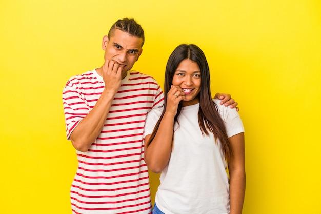 Giovane coppia latina isolata su sfondo giallo che si morde le unghie, nervosa e molto ansiosa.