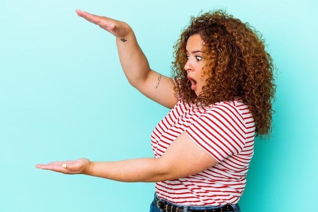 Giovane donna curvy latina isolata sulla parete blu scioccata e stupita tenendo uno spazio di copia tra le mani.