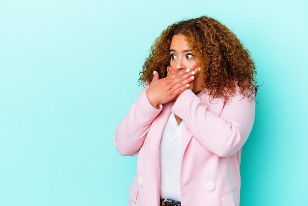 Giovane donna curvy latina isolata sulla parete blu premurosa alla ricerca di uno spazio di copia che copre la bocca con la mano.