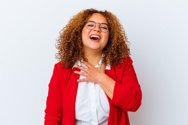 La giovane donna curvy latina isolata su fondo bianco ride ad alta voce tenendo la mano sul petto.
