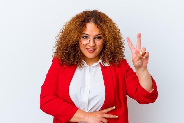 Giovane donna curvy latina isolata su fondo bianco che mostra il numero due con le dita.