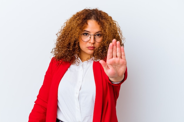 Giovane donna curvy latina isolata sul muro bianco in piedi con la mano tesa che mostra il segnale di stop, impedendoti