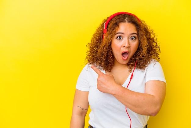 Giovane donna curvy latina che ascolta musica isolata su fondo giallo che indica il lato