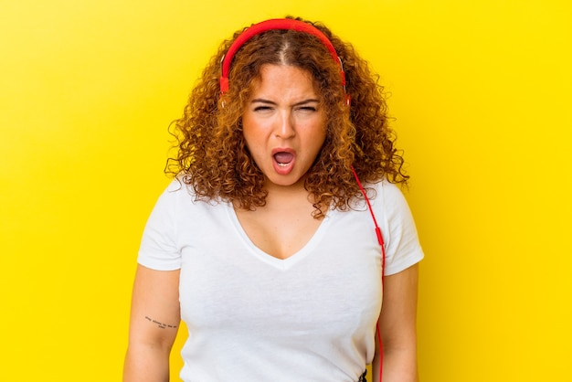 Giovane donna curvy latina che ascolta musica isolata su sfondo giallo urlando molto arrabbiata e aggressiva.