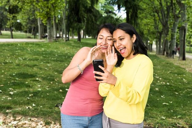 La giovane donna latina in una videochiamata con uno smartphone con gli amici causa la distanza sociale conferenza in bolivia in sud america usando la tecnologia