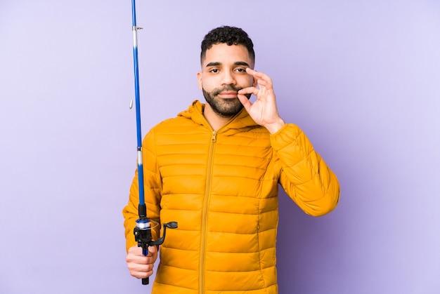 Giovane pescatore latino che tiene una canna giovane pescatore latino che tiene in mano un giovane uomo latino che gioca a canestro con le dita sulle labbra mantenendo un segreto. <mixto>
