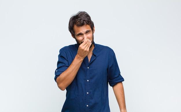 Giovane bell'uomo latino che si sente disgustato, tenendo il naso per evitare di annusare un fetore sgradevole e sgradevole