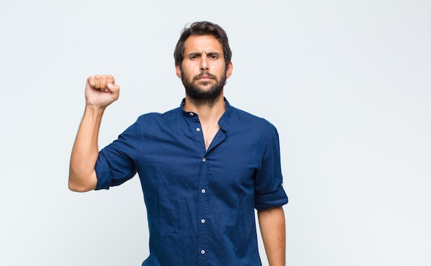 Giovane bell'uomo latino che si sente serio, forte e ribelle, alza il pugno, protesta o combatte per la rivoluzione