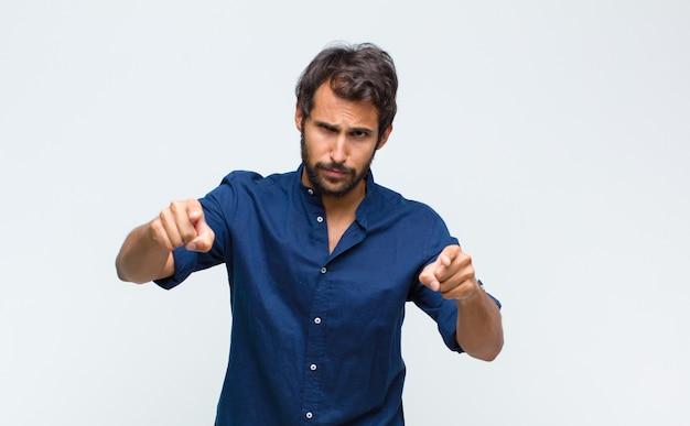 Giovane uomo bello latino che punta in avanti verso la telecamera con entrambe le dita e l'espressione arrabbiata