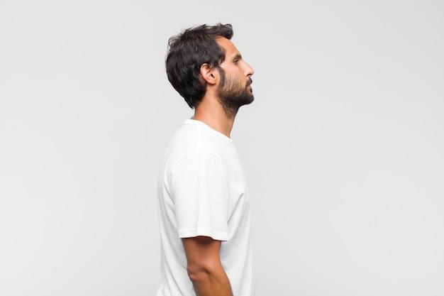 Giovane uomo bello latino sulla vista di profilo che cerca di copiare lo spazio davanti, pensare, immaginare o sognare ad occhi aperti