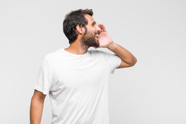 Vista di profilo del giovane uomo bello latino, che sembra felice ed eccitato, gridando e chiamando per copiare lo spazio sul lato