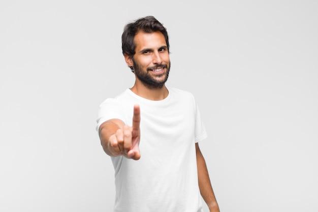 Giovane bell'uomo latino che sorride con orgoglio e sicurezza facendo il numero uno in posa trionfante, sentendosi come un leader