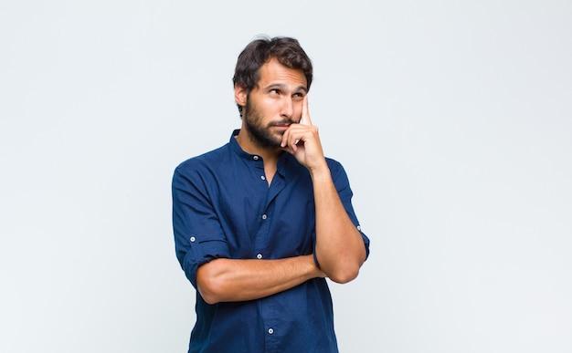 Giovane bell'uomo latino con uno sguardo concentrato, chiedendosi con un'espressione dubbiosa, guardando in alto e di lato