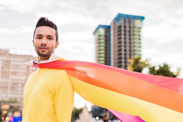Giovane uomo omosessuale latino con la bandiera arcobaleno della parata del gay pride stile di vita supereroe capo
