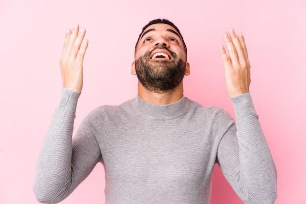 Il giovane latino contro una parete rosa ha isolato le grida al cielo, guardante su, frustrato.
