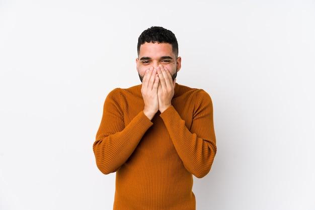 Giovane uomo latino contro uno sfondo bianco isolato ridendo di qualcosa, coprendo la bocca con le mani.
