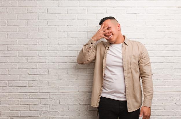 Giovane uomo latino imbarazzato e ridente allo stesso tempo
