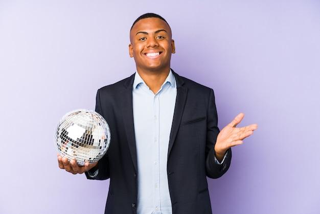 Giovane uomo latino in possesso di un partito palla isolato ricevendo una piacevole sorpresa, eccitato e alzando le mani.