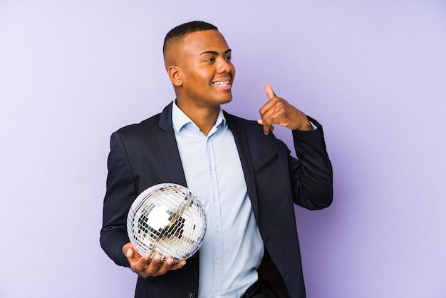 Giovane uomo latino che tiene una festa della palla isolata che mostra un gesto di chiamata di telefono cellulare con le dita.