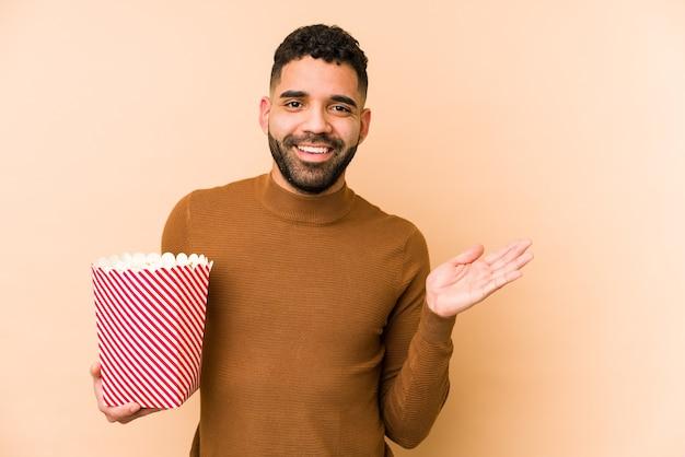 Giovane uomo latino che tiene un pop corn isolato mostrando uno spazio di copia su un palmo e tenendo un'altra mano sulla vita.