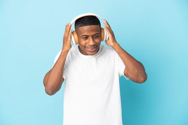 Giovane uomo latino isolato su musica d'ascolto blu