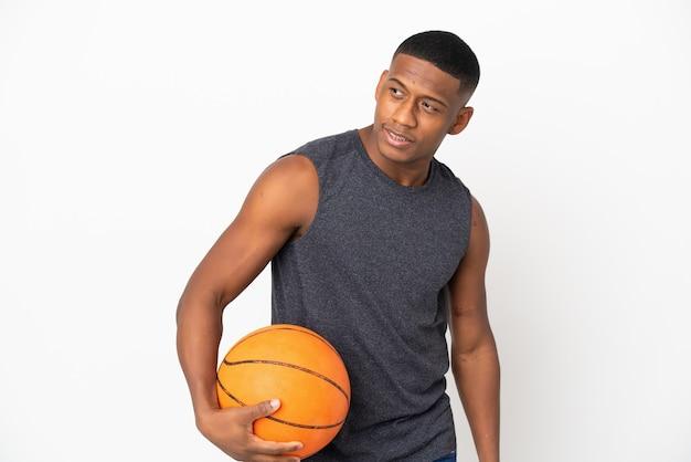 Giovane uomo latino isolato giocando a basket e avendo un'idea