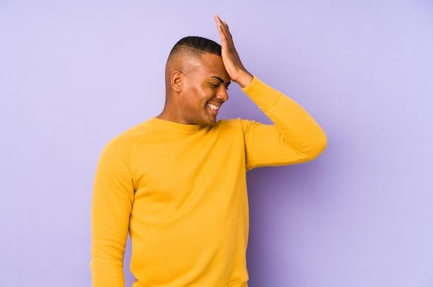 Giovane uomo latino isolato su sfondo viola dimenticando qualcosa, schiaffi sulla fronte con il palmo e chiudendo gli occhi.