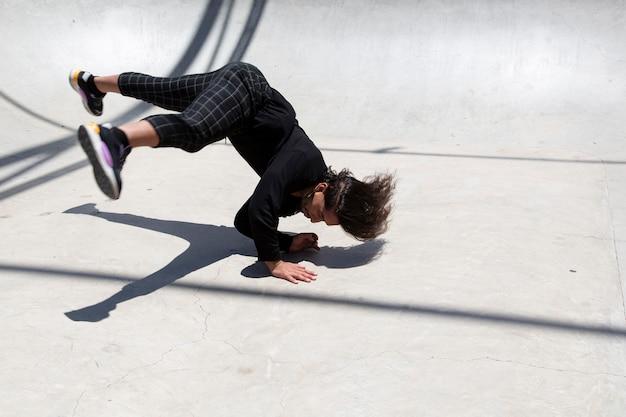 Giovane uomo latino che esegue street dance all'interno della fossa di pattinaggio.