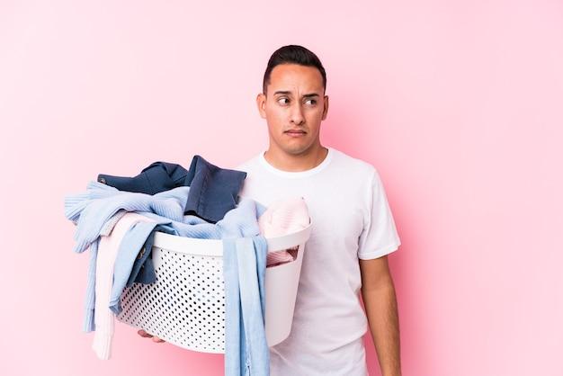 Il giovane latino che raccoglie vestiti sporchi isolati confuso, si sente dubbioso e insicuro.