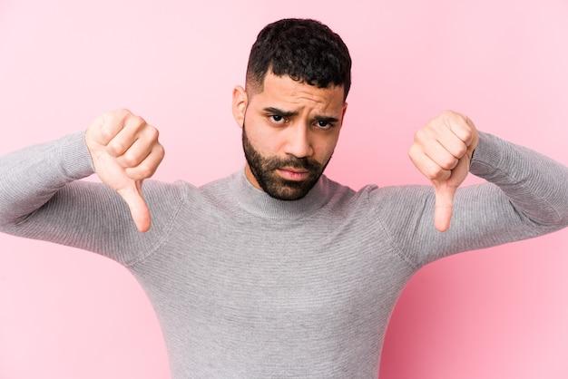 Giovane uomo latino in rosa isolato che mostra il pollice verso il basso ed esprime antipatia.