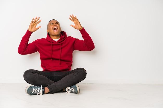 Giovane uomo latino seduto sul pavimento isolato urlando al cielo, guardando in alto, frustrato.